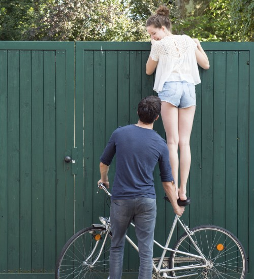 guy helping girl on bike